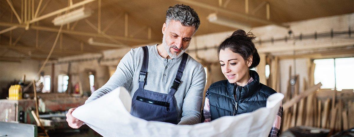 Un homme et une femme en atelier regardant un plan